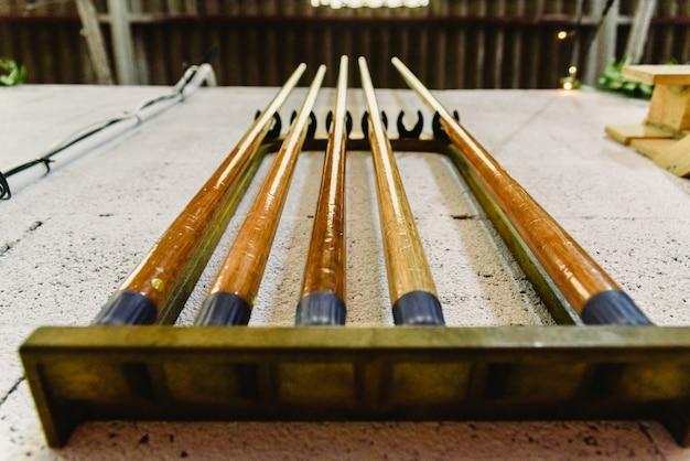 Varas para jogar bilhar pendurado na parede. Foto Premium