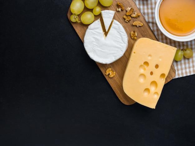 Variação de queijo, nozes, mel e uvas na tábua de madeira. queijo camembert e queijo edam. alimento para o vinho e romântico, da vista superior. Foto Premium
