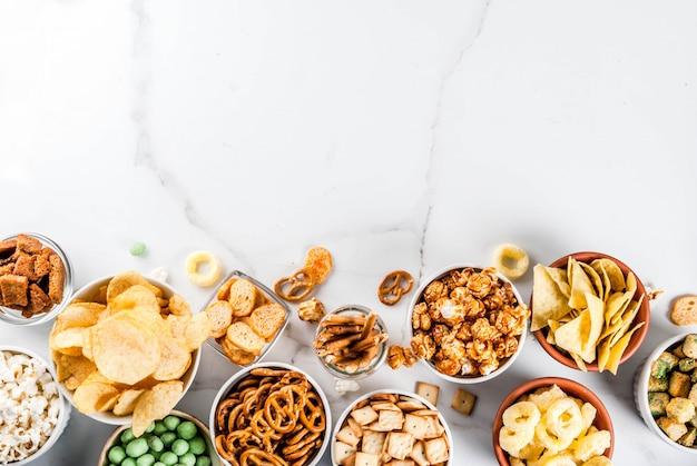 Variação diferentes biscoitos salgadinhos salgadinhos, pipoca salgada doce, tortilhas, nozes, palhas, bretsels, fundo de mármore branco cópia lanches salgados Foto Premium