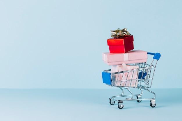 Várias caixas de presente empilhadas no carrinho de compras em fundo azul Foto gratuita