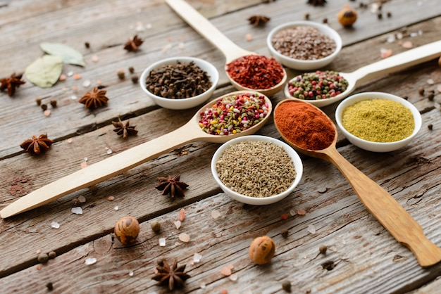 Várias especiarias contra um fundo escuro. ingredientes alimentares. pode ser usado como pano de fundo Foto Premium