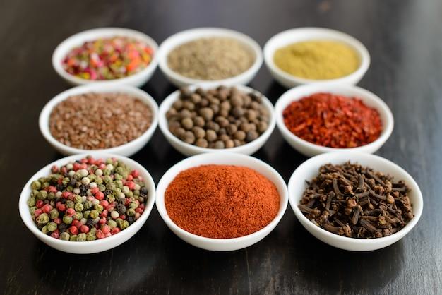 Várias especiarias contra um fundo escuro. ingredientes alimentares Foto Premium