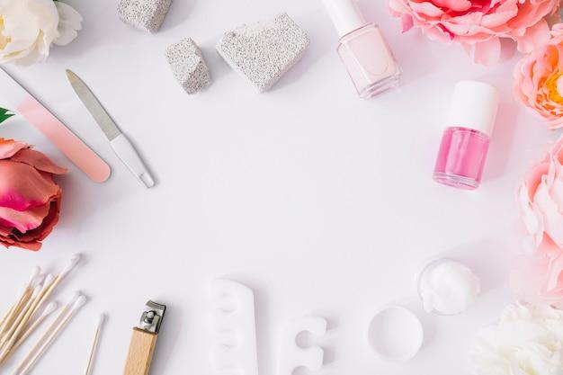 Várias ferramentas de manicure e produtos em fundo branco Foto gratuita