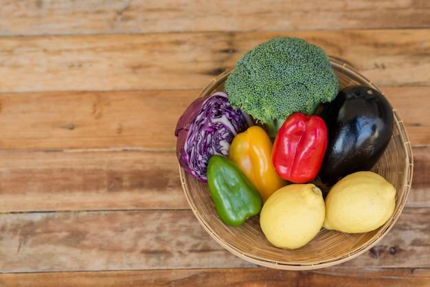 Várias frutas com vegetais no fundo de madeira Foto gratuita