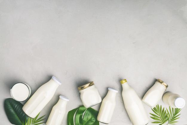 Várias garrafas de leite e folhas tropicais Foto Premium