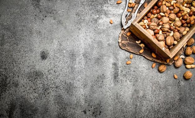 Várias nozes em uma velha caixa e um quebra-nozes. Foto Premium