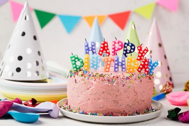 Variedade com bolo rosa para festa de aniversário Foto gratuita