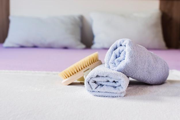 Variedade com toalhas e escova na cama Foto gratuita