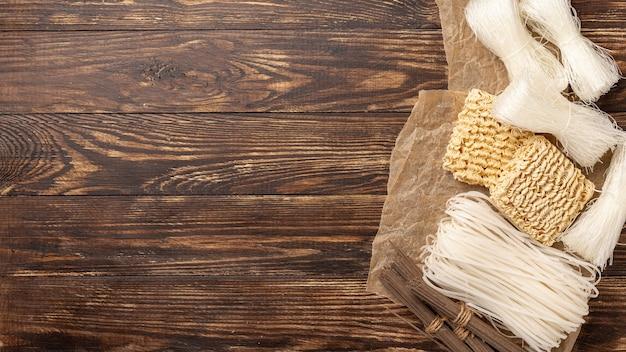 Variedade crua plana leiga de macarrão no fundo de madeira com espaço de cópia Foto gratuita