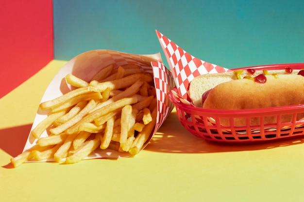 Variedade de alto ângulo com batatas fritas e cachorro-quente na cesta Foto gratuita