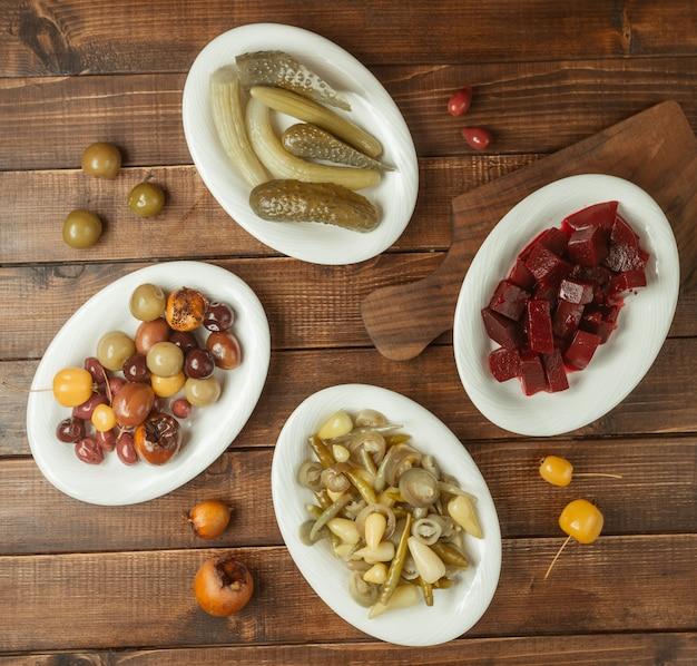 Variedade de aperitivos, seleções de alimentos marinados em pratos brancos Foto gratuita