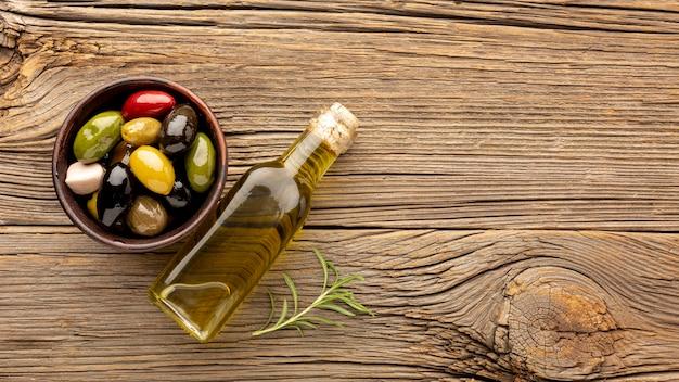 Variedade de azeitonas coloridas com espaço para garrafa e cópia de óleo Foto gratuita