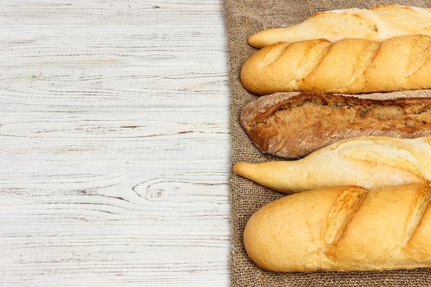 Variedade de baguetes francesas frescas sobre um fundo de mesa de madeira Foto Premium