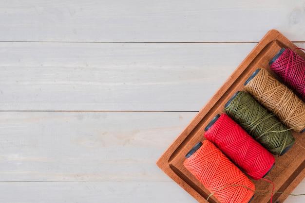 Variedade de carretéis coloridos brilhantes na bandeja de madeira sobre a mesa branca Foto gratuita