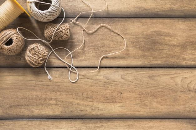 Variedade de carretel de corda na mesa de madeira Foto gratuita