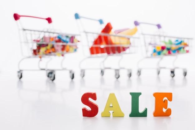 Variedade de carrinho de compras com sinal de venda Foto gratuita