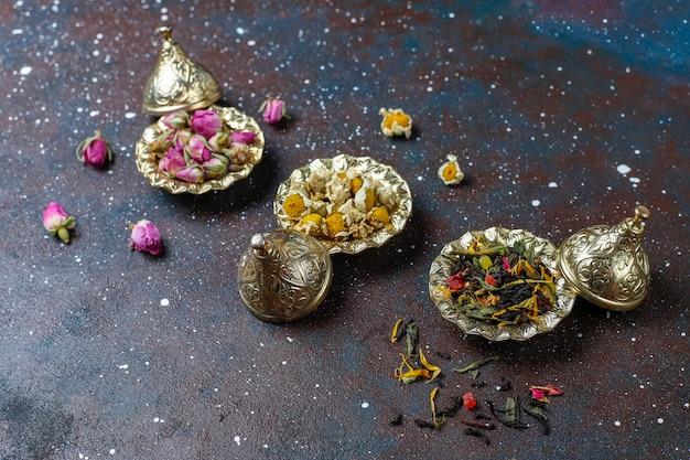 Variedade de chá seco em mini placas vintage douradas. fundo de tipos de chá Foto gratuita
