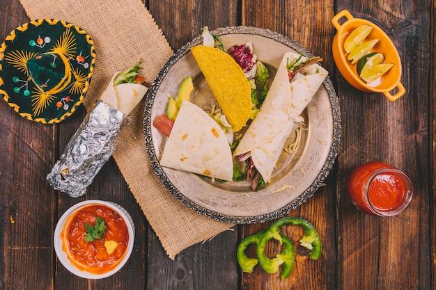 Variedade de comida mexicana com chapéu na mesa de madeira Foto gratuita