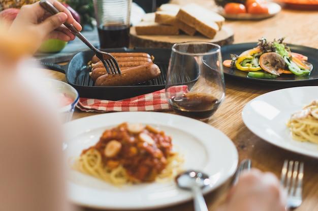 Variedade de comida na mesa de madeira e amigos jantando juntos. Foto Premium