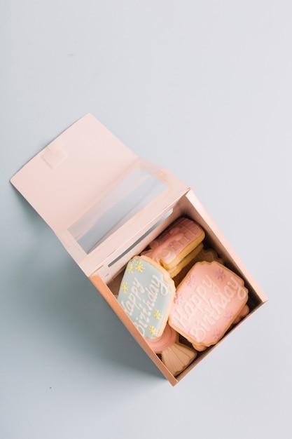 Variedade de cookies com texto de feliz aniversário em caixa de presente, isolada no fundo branco Foto gratuita