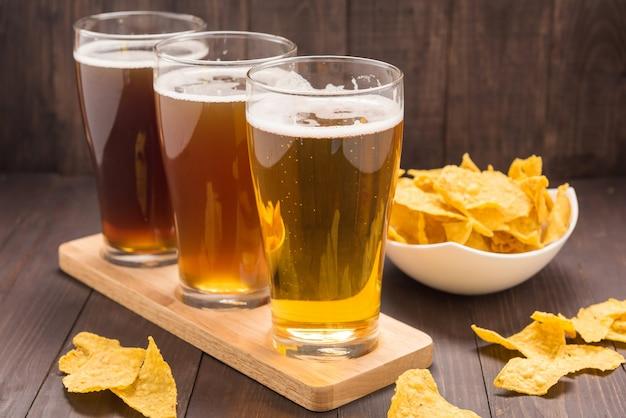 Variedade de copos de cerveja com chips de nachos em uma mesa de madeira. Foto Premium
