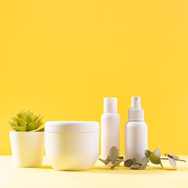 Variedade de cosméticos com fundo amarelo Foto gratuita