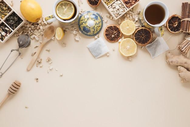 Variedade de ervas; colher; dipper de mel; coador de chá; frutas e ingredientes de uvas secas Foto gratuita