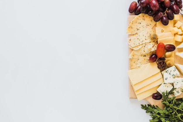 Variedade de fatias de queijo e cubos com uvas, tomate e salsa no fundo branco Foto gratuita
