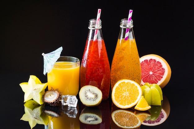 Variedade de frutas e sucos em fundo preto Foto gratuita