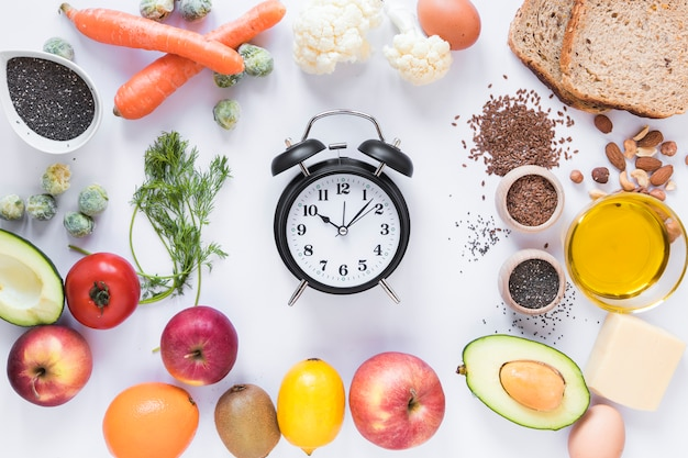 Variedade de ingredientes com despertador organizado contra isolado no fundo branco Foto gratuita