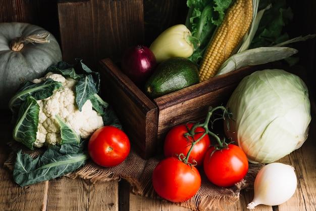 Variedade de legumes e uma cesta de madeira Foto gratuita