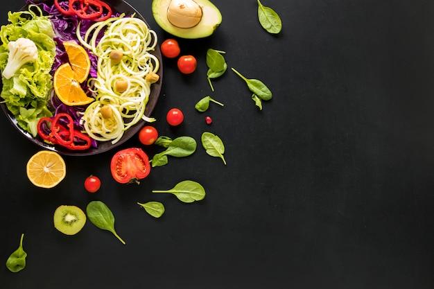 Variedade de legumes frescos picados e frutas em fundo preto Foto gratuita