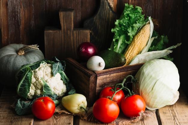 Variedade de legumes saborosos e tomates em fundo de madeira Foto gratuita