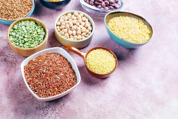 Variedade de leguminosas e feijão em tigelas diferentes sobre fundo de pedra clara. vista do topo. alimentos saudáveis de proteína vegana. Foto gratuita