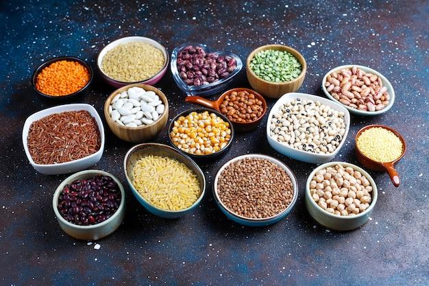 Variedade de leguminosas e feijões em diferentes tigelas Foto gratuita