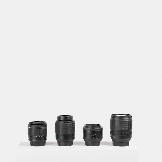 Variedade de lentes de câmera dispostas na mesa na frente do fundo branco Foto gratuita