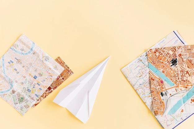 Variedade de mapas com avião de papel branco sobre fundo bege Foto gratuita
