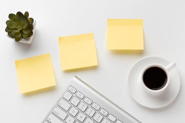 Variedade de mesa de escritório plana com post-its vazios Foto gratuita