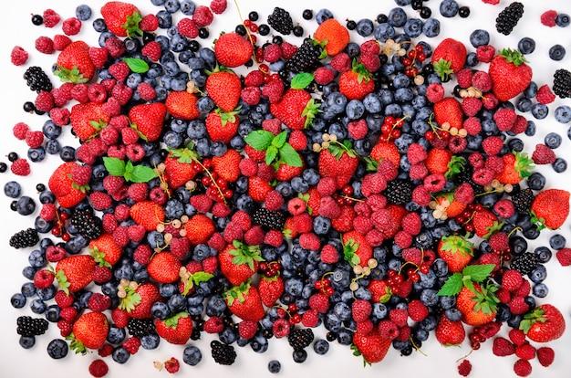 Variedade de morango, mirtilo, groselha, folhas de hortelã. fundo de bagas de verão. quadro de comida e design de fronteira. vegan, conceito vegetariano. Foto Premium