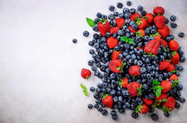 Variedade de morango, mirtilo, groselha, folhas de hortelã. quadro de comida, design de fronteira. conceito vegan e vegetariano. fundo de bagas de verão Foto Premium