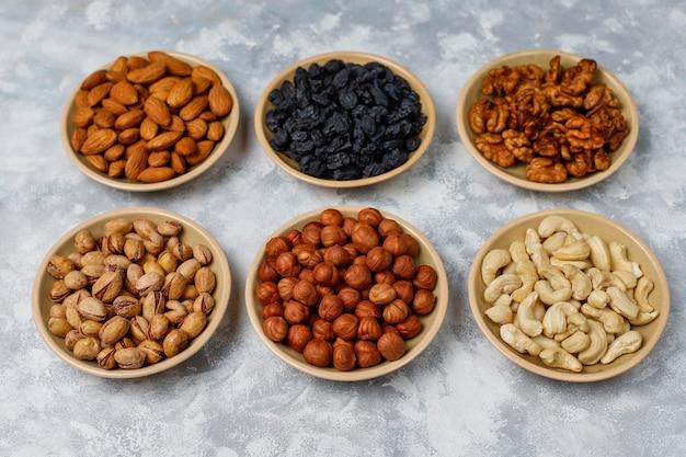 Variedade de nozes em pratos de cerâmica. caju, avelãs, nozes, pistache, nozes, pinhões, amendoim, passas. vista superior Foto gratuita