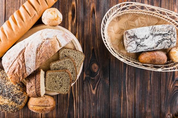 Variedade de pães recém-assados no prato e cesta sobre o pano de fundo de madeira Foto gratuita