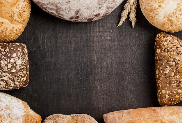 Variedade de pão cozido e cópia espaço preto fundo Foto gratuita