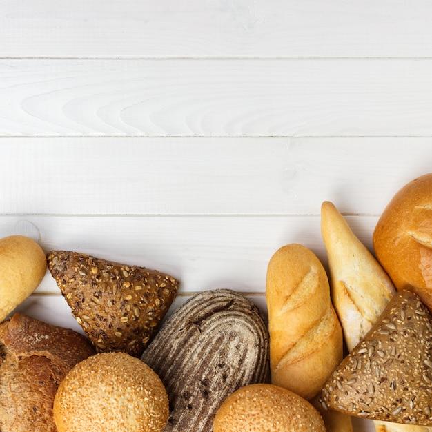 Variedade de pão no fundo da mesa de madeira branca. vista superior com espaço de cópia Foto Premium