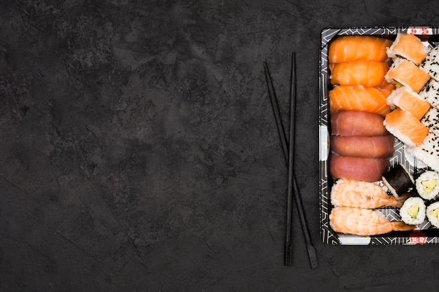 Variedade de peixe asiático rola na bandeja e pauzinhos sobre o plano de fundo texturizado com espaço para texto Foto gratuita
