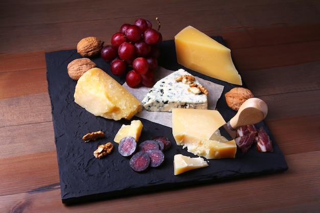 Variedade de queijo com frutas, uvas, nozes e faca de queijo em uma bandeja de servir de madeira. Foto Premium