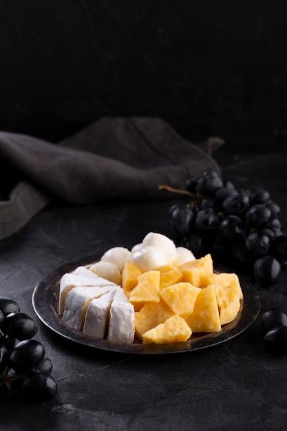 Variedade de queijo com uvas pretas Foto gratuita
