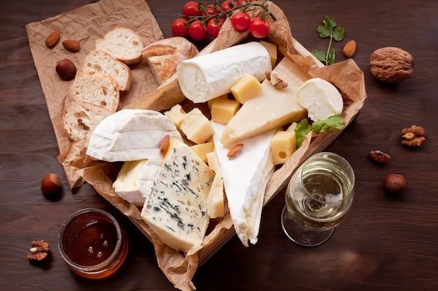 Variedade de queijos diferentes com vinho, frutas e nozes. camembert, queijo de cabra, roquefort, gorgonzolla, gauda, parmesão, emmental Foto Premium