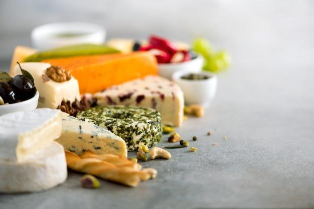 Variedade de queijos duros, semi-moles e macios, com azeitonas, varas de pão grissini, alcaparras, uva Foto Premium
