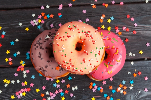 Variedade de rosquinhas coloridas decoradas com confetes coloridos Foto Premium